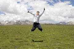 Young man jumps high. In grassland near snow mountain under blue sky Royalty Free Stock Photos