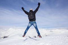 Young man jumps for joy in the snowy mountains Stock Photo