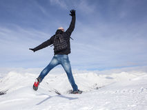 Young man jumps for joy in the snowy mountains Royalty Free Stock Images