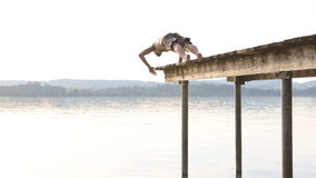 Young man jumps off the dock into water stock video footage