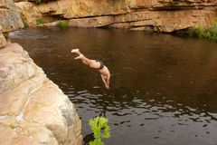 Young man jumps into river Royalty Free Stock Photography