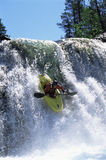 Young man kayaking down waterfall Stock Images