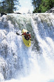 Young man kayaking down waterfall Royalty Free Stock Photo