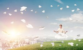 Young man keeping mind conscious. Young man keeping eyes closed and looking concentrated while meditating on cloud among flying paper planes with city view on Stock Photography