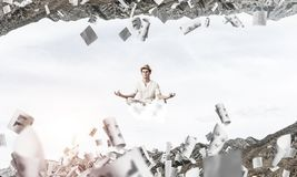 Young man keeping mind conscious. Young man keeping eyes closed and looking concentrated while meditating on cloud among flying papers and between two nature Royalty Free Stock Photo