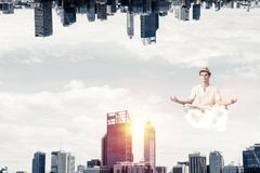 Young man keeping mind conscious. Young man keeping eyes closed and looking concentrated while meditating on cloud in the air between two urban worlds Stock Images