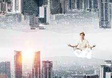 Young man keeping mind conscious. Young man keeping eyes closed and looking concentrated while meditating on cloud in the air between two urban worlds Royalty Free Stock Images