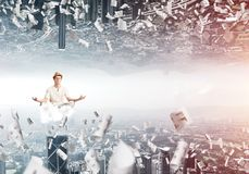 Young man keeping mind conscious. Young man keeping eyes closed and looking concentrated while meditating on cloud among flying papers and between two worlds Royalty Free Stock Images