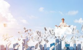 Young man keeping mind conscious. Man in white clothing keeping eyes closed and looking concentrated while meditating on cloud among flying papers with Stock Photos