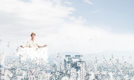 Young man keeping mind conscious. Man in white clothing keeping eyes closed and looking concentrated while meditating on cloud among flying letters with Stock Photography