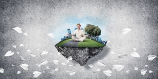 Young man keeping mind conscious. Man in white clothing keeping eyes closed and looking concentrated while meditating on island in the air among flying paper Royalty Free Stock Photo