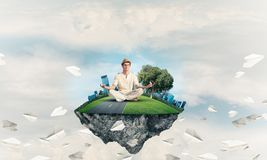 Young man keeping mind conscious. Man in white clothing keeping eyes closed and looking concentrated while meditating on island in the air among flying paper Royalty Free Stock Photography