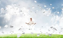 Young man keeping mind conscious. Young man keeping eyes closed and looking concentrated while meditating on cloud among flying paper planes with bright and Royalty Free Stock Photography