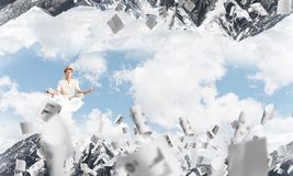 Young man keeping mind conscious. Young men keeping eyes closed and looking concentrated while meditating on cloud among flying papers and between two nature Stock Image