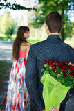 Young man keeps behind his back a bouquet of red roses gift a hi. S girlfriend in a summer park Royalty Free Stock Images