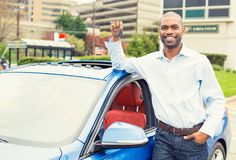 Young man with the keys standing by his new car Stock Photo