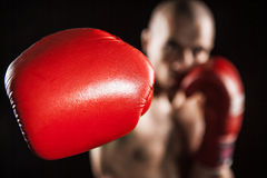 The young man kickboxing on black stock photos