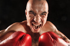 The young man kickboxing on black  with screaming face Stock Photo