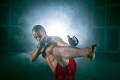 The young man kickboxing in blue smoke Royalty Free Stock Photography
