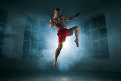 The young man kickboxing in blue smoke stock image