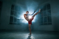 The young man kickboxing in blue smoke. The young male athlete kickboxing on a background of blue smoke Stock Photography