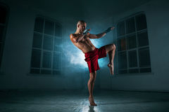 The young man kickboxing in blue smoke stock images