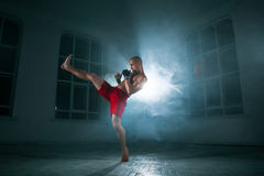 The young man kickboxing in blue smoke royalty free stock photos