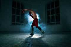 The young man kickboxing in blue smoke stock photos