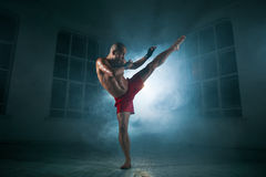 The young man kickboxing in blue smoke royalty free stock image