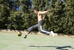 Young man kicking ball Stock Photography