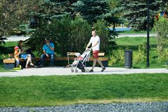 Young man with kids stroller walking in Butovo park, Moscow, Russia stock images