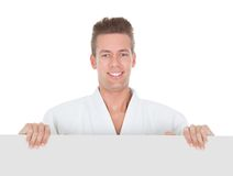 Young Man In Kimono Holding Placard Royalty Free Stock Photography