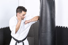 Young man in kimono throwing punches at a heavy punching bag Stock Photos