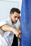 Young man in kimono throwing punches at a heavy punching bag Royalty Free Stock Photos