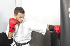 Young man in kimono throwing punches at a heavy punching bag Stock Image