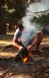 Young man kindling firewood in the forest Royalty Free Stock Photo