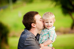 A young man kisses his little son Stock Photo
