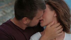 Young man kisses woman sitting on sea shore in summer evening outdoors. Bearded male holds tanned neck of female with hand, gently touches her lips and slowly stock video footage