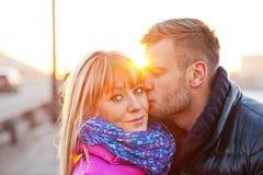 Young man kissing a beautiful woman Stock Photos