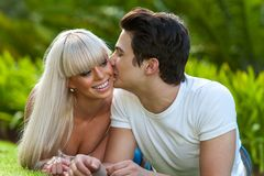 Young man kissing girlfriend on cheek. Royalty Free Stock Image