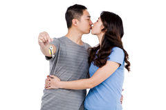 Young man kissing girlfriend while showing keys Stock Photo