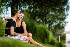 Young man kissing his girlfriend on cheeks Stock Image