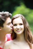 Young man kissing his girlfriend Royalty Free Stock Photos