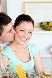 Young man kissing his girlfriend preparing pasta Royalty Free Stock Photo