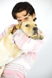 Young man kissing his puppy dog labrador Stock Photography