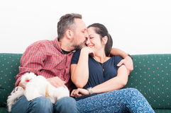 Young man kissing his wife on the couch Royalty Free Stock Photos