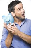 Young Man kissing Piggy bank Royalty Free Stock Photos