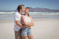 Young man kissing woman at beach. During sunny day Royalty Free Stock Photography
