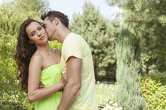 Young man kissing woman in park Stock Images