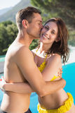 Young man kissing woman by swimming pool Stock Image